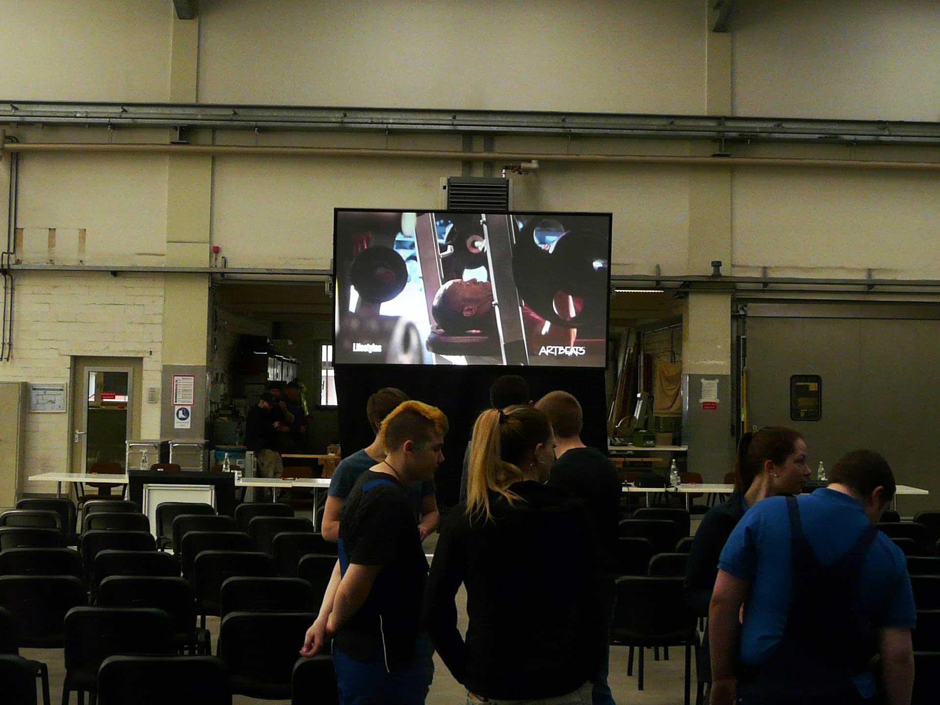 Revosoft's Team Leinwand und Beamer Vermietung Lübeck ermöglichte mit einer Gain 26 Hellraumleinwand und einem 15.000 ASNI Lumen 2K LCD Projektor trotz Einfall von Tageslicht eine brillante und gut lesbare Großbildprojektion in einer Produktionshalle für eine Betriebsratssitzung. Projektor leihen